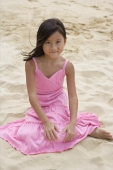 Young girl sitting in the sand and smiling at camera - Yukmin