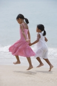 Sisters running on the beach and holding hands - Yukmin