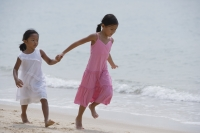Sisters running while holding hands at the beach - Yukmin