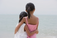 Young sisters hugging and looking out at sea - Yukmin