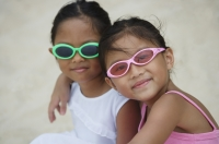 Two young sisters with sunglasses hugging - Yukmin
