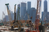 Cranes at construction site in front of cityscape - Yukmin