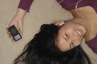 Young woman listening to music - Yukmin