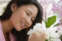 Young woman smiling at flower - Yukmin