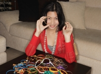 Young woman with many bracelets on table - Yukmin