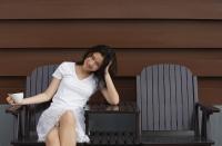 Young woman enjoying cup of tea in garden chair - Yukmin
