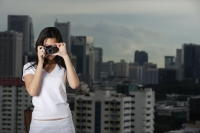 Young woman taking photograph - Yukmin
