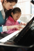 Piano teacher and girl playing piano - Alex Mares-Manton