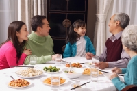 Family at dinner table having traditional food, girl standing next to grandfather - Alex Mares-Manton