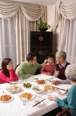 Family at dinner table having traditional food, boy standing next to grandfather - Alex Mares-Manton