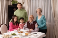 Family at dinner table with traditional food - Alex Mares-Manton