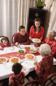Family at dinner table having traditional food - Alex Mares-Manton