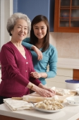 Mother and daughter making dumplings in the kitchen - Alex Mares-Manton