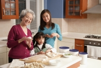 Grandmother, daughter and granddaughter making dumplings in the kitchen, looking at camera - Alex Mares-Manton
