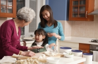 Grandmother, daughter and granddaughter making dumplings in the kitchen - Alex Mares-Manton