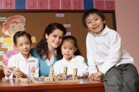 Young school children with their teacher in classroom - Alex Mares-Manton
