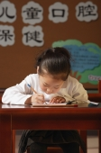 Schoolgirl writing at the desk - Alex Mares-Manton