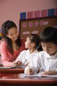 Students in class with teacher looking at schoolgirl - Alex Mares-Manton