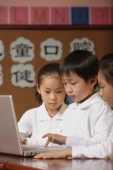 Young students using laptop in class, schoolboy typing on keypad - Alex Mares-Manton