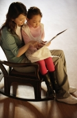 Mother and daughter on rocking chair reading a book - Alex Mares-Manton