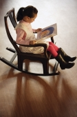 Girl sitting in rocking chair, reading a book - Alex Mares-Manton