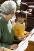 Girl playing piano with grandmother - Alex Mares-Manton