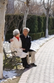 Elderly couple sitting on park bench - Alex Mares-Manton