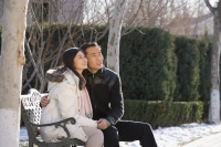 Young couple sitting on park bench - Alex Mares-Manton