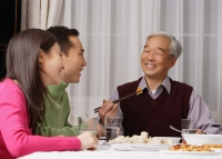 Young couple and elderly father at dinner table - Alex Mares-Manton