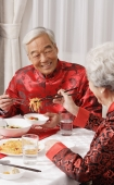 Elderly couple in traditional clothing at dinner table - Alex Mares-Manton