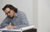 Man sitting at desk drawing - Yukmin