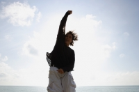 Man at beach jumping in the air with arm raised - Yukmin
