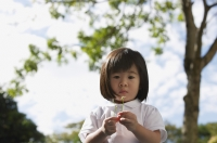 Young girl at park with flower, looking at camera - Yukmin