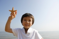 Young boy holding shell at the beach - Yukmin