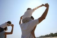 Young couple piggybacking children at the beach - Yukmin