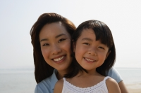 Mother and daughter at the beach, smiling at camera - Yukmin