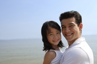 Father and daughter at the beach, looking at camera - Yukmin