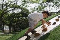 Young boy playing on rock-climbing wall - Yukmin