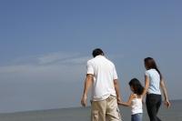 Family holding hands, walking down the beach - Yukmin
