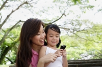 Mother and daughter at the park looking at cellphone - Yukmin