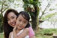 Mother and daughter at the park, both looking at camera - Yukmin