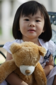 A young girl looking at camera, holding teddy bear - Yukmin