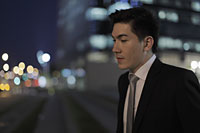 Profile of young man in front of buildings at night - Alex Mares-Manton