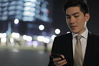 Young man texting on phone at night, buildings in background - Alex Mares-Manton