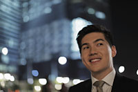 Head shot of young man looking up and smiling, lit buildings in background - Alex Mares-Manton