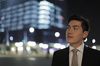 Man wearing a suit looking off, lit buildings in background. - Alex Mares-Manton