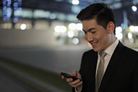 Man wearing a business suit, smiling at phone at night - Alex Mares-Manton