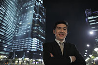 Man wearing a suit standing in front of lit buildings at night - Alex Mares-Manton