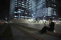 Man sitting on ground working on lap top in front of lit buildings - Alex Mares-Manton