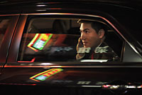 Man sitting in car talking on phone. Chinese characters reflected on the windows - Alex Mares-Manton